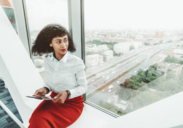 A beautiful African-American woman entrepreneur in a white blouse and red skirt is holding a digital tablet pc while sitting indoors on the bench on the top floor of a business office skyscraper
